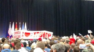 """Crowd members hold a banner reading """"Chinese Americans (heart) Trump"""""""