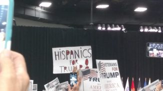 """Crowd members hold signs reading """"Hispanics For Trump"""" and """"Veterans For Trump"""""""